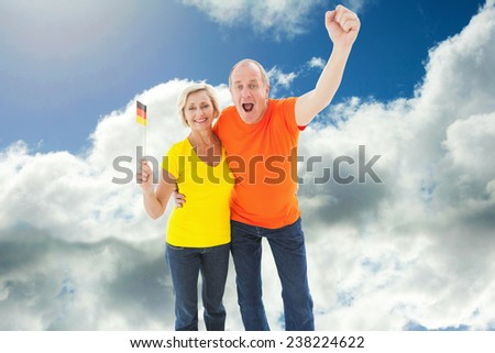 Happy german couple cheering at camera against blue sky with clouds - stock photo