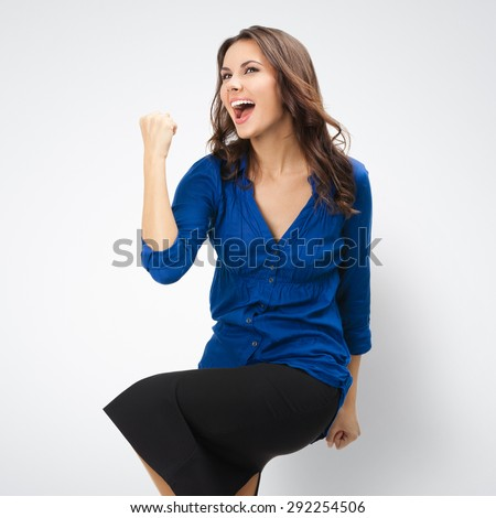 Happy gesturing young cheerful gesturing businesswoman, posing at studio against grey background  - stock photo