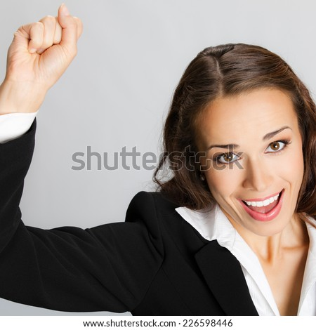 Happy gesturing young cheerful smiling business woman, against grey background - stock photo