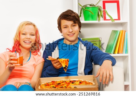 Happy girl and boy hold pizza pieces on white sofa - stock photo