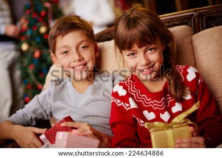 Happy girl and boy with Christmas gifts looking at camera - stock photo