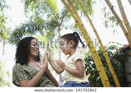 Happy girl and mother playing patty cake in park - stock photo