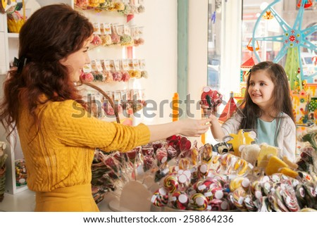 Happy girl buying sweets in the store. Beautiful woman salesman gives candies to girl  - stock photo
