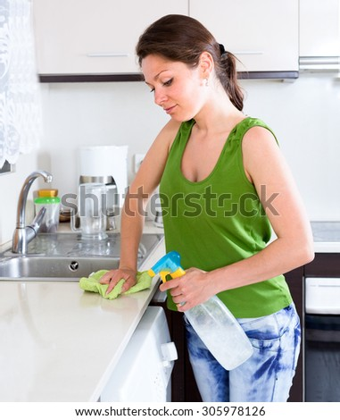 Happy girl cleaning  furniture in kitchen at home