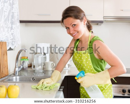 Happy girl cleaning furniture in kitchen at home - stock photo