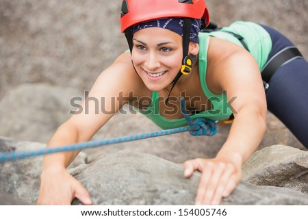 Happy girl climbing rock face wearing red helmet - stock photo