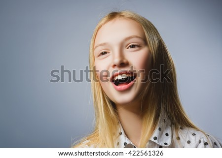 Happy girl. Closeup  Portrait of handsome teen in casual shirt smiling while standing against grey background - stock photo