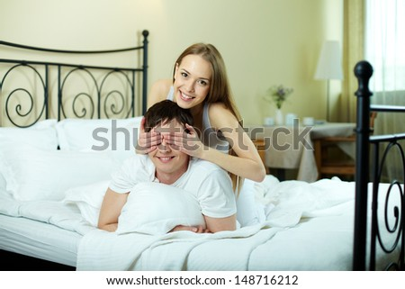 Happy girl closing her boyfriend eyes by hands in bed - stock photo