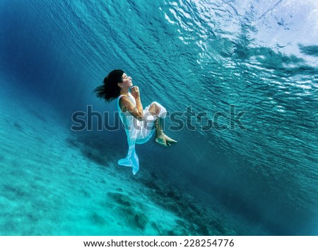 Happy girl dancing underwater, wearing stylish dress, luxury sea performance, active summer vacation, sport and art concept - stock photo