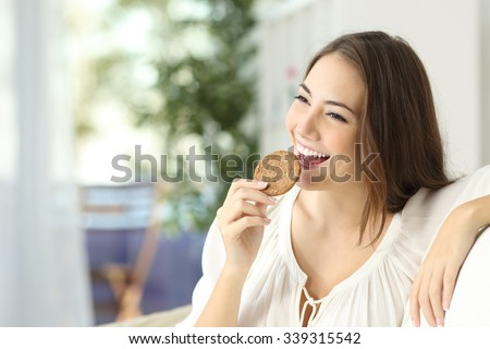 Happy girl eating a dietetic cookie sitting on a couch at home - stock photo