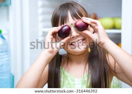Happy girl eating plums standing near refrigerator with fruits and vegetables