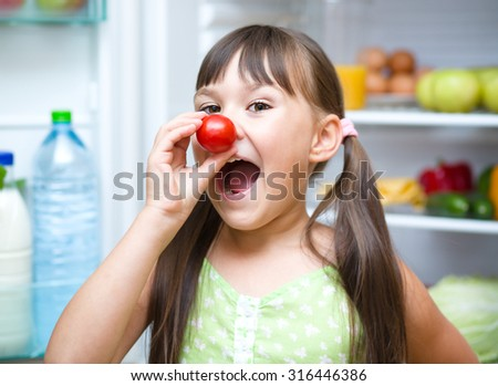Happy girl eating tomatoes standing near refrigerator with fruits and vegetables - stock photo