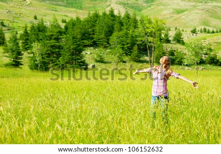 Happy girl enjoying nature, young woman on wheat field, beautiful female having fun with hands up, freedom concept, summer outdoor vacation, model teen over green natural background, sunny day joy - stock photo