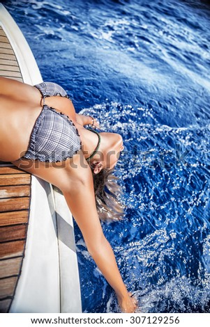 Happy girl enjoying sea touch, sexy female tanning on sailboat, active lifestyle, relaxation among the sea, joyful summer vacation - stock photo