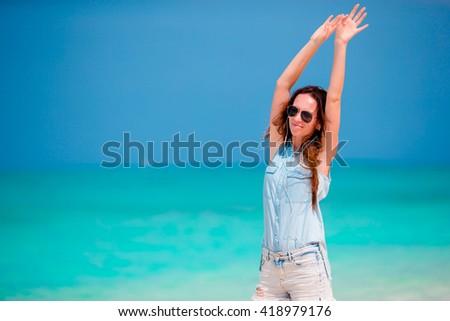 Happy girl enjoying the music on white sandy beach - stock photo
