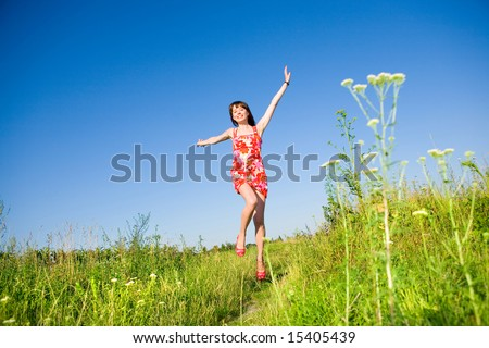 Happy girl fleeing on a meadow. In red dress and red shoes. Against the backdrop of blue sky.