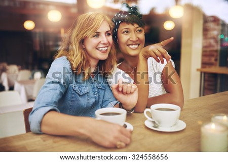 Happy girl friends enjoying coffee together in a coffee house sitting pointing and smiling with amusement as they watch something to the right of the screen, multi ethnic young lady friends - stock photo
