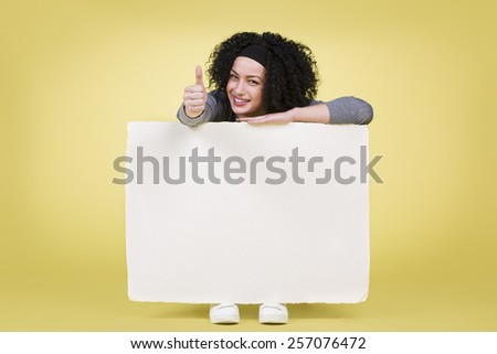 Happy girl holding a white blank paper sign board with empty copy space and giving thumbs up, isolated on yellow background. - stock photo