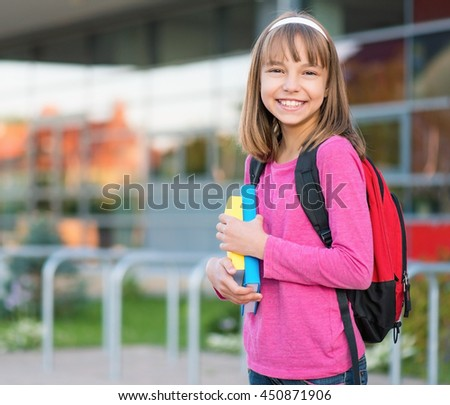 Happy girl holding books in school yard. Outdoor portrait. - stock photo