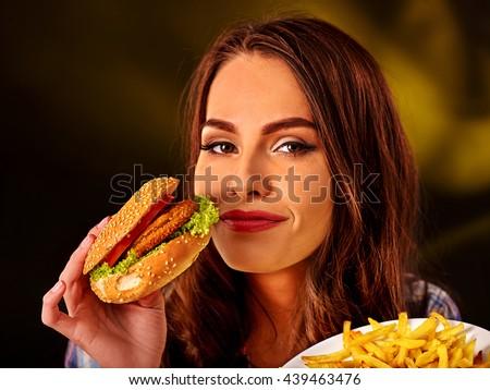 Happy girl holding fastfood hamburger and fried potatoes . Fastfood concept fastfood hamburger and fried potatoes on green. Dark background. - stock photo