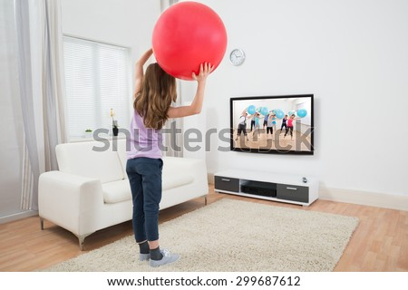 Happy Girl Holding Fitness Ball In Front Of Television At Home