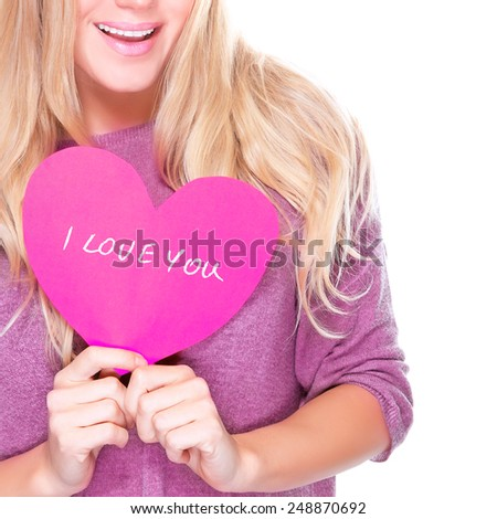 Happy girl holding in hands pink heart shaped greeting card with text isolated on white background, i love you, face part, Valentine day - stock photo