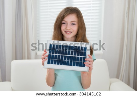 Happy Girl Holding Solar Panel In Living Room - stock photo