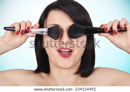 happy girl holding two makeup brush, close up - stock photo