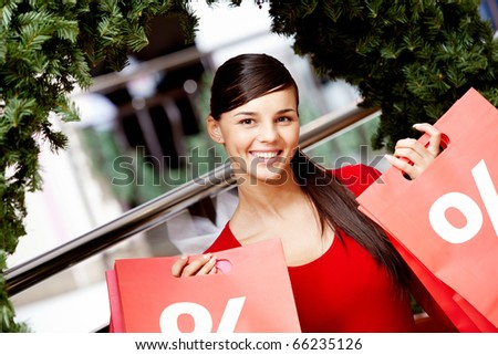 Happy girl holds red paperbags with symbol of sale in market - stock photo