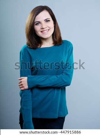 happy girl in a blue shirt on a gray background - stock photo