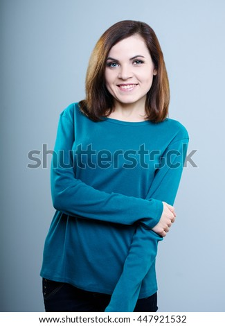 happy girl in a blue shirt on a gray background