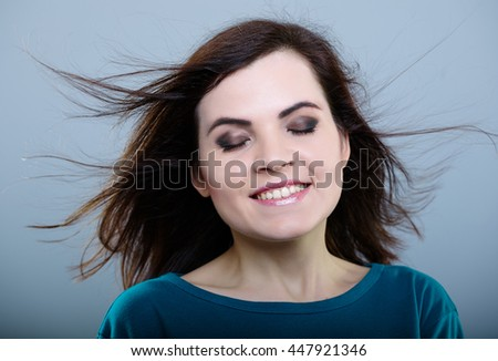 happy girl in a blue t-shirt with flying hair on gray background