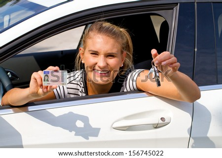 Happy girl in a car showing a key and her driver license - stock photo