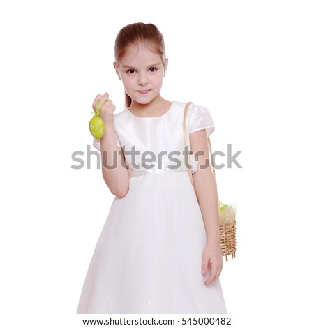 Happy girl in a white dress holding colored easter egg