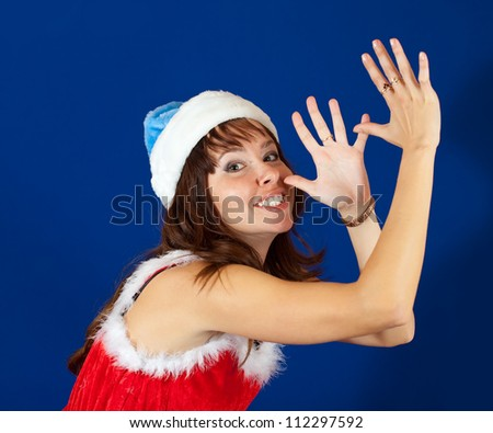 Happy girl in  christmas costume over blue background