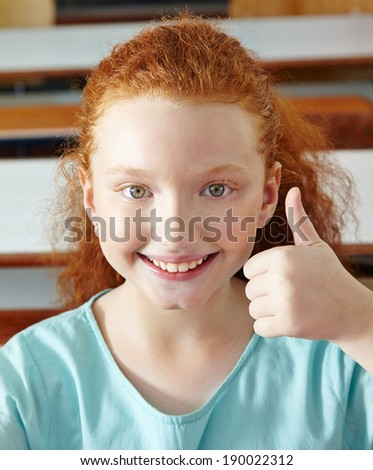 Happy girl in elementary school holding her thumbs up - stock photo