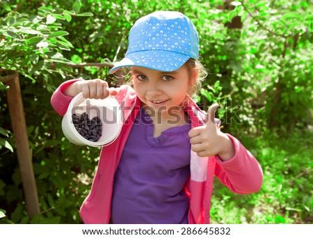 Happy girl in garden with early ripe berries honeysuckle - stock photo