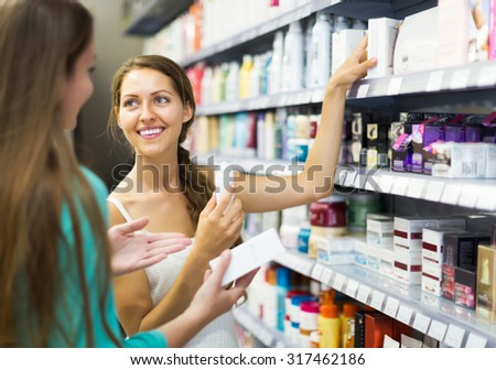 Happy girl in good spirits selecting cosmetical cream in the store - stock photo