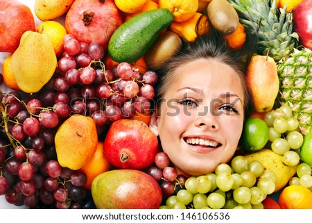 Happy girl in group of fruit.