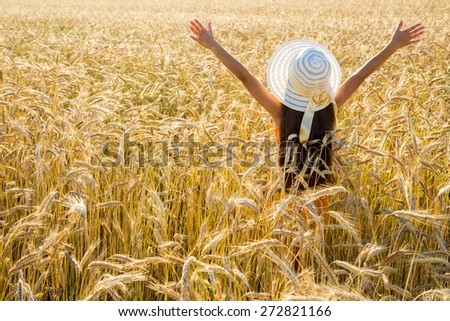Happy girl in hat on wheat field, with space for text - stock photo