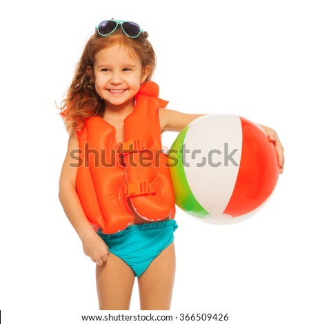 Happy girl in lifejacket with colored rubber ball - stock photo