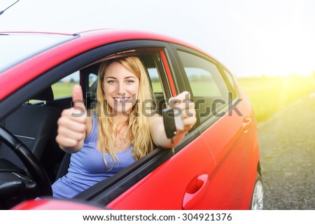 Happy girl in red car showing thumb up and key.