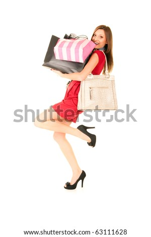 happy girl in red dress wearing black shoes try to hold her paper bags