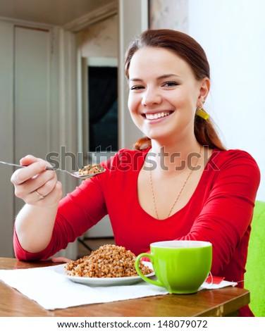 Happy girl in red eats buckwheat with spoon - stock photo