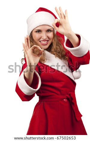 Happy girl in Santa Claus hats showing okay sign - stock photo
