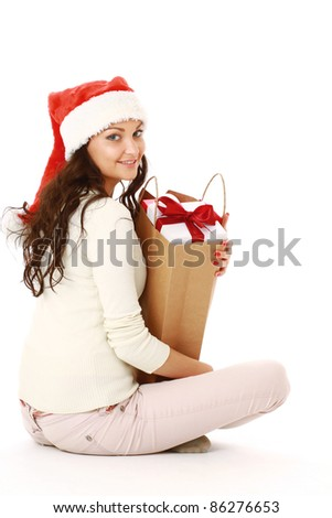 Happy girl in santa hat sitting cross-legged with bag full of xmas gifts isolated on white background