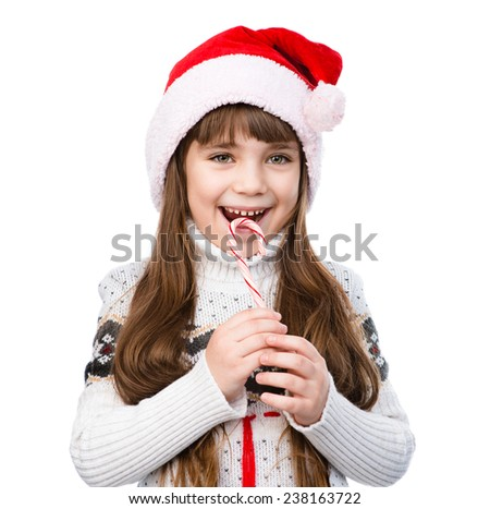 happy girl in santa hat with Christmas candy cane. isolated on white background - stock photo