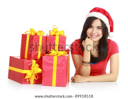 Happy girl in santa hat with pile of xmas gifts  isolated on white background - stock photo