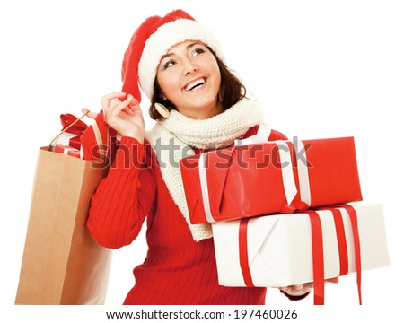 Happy girl in santa hat with pile of xmas gifts looking at copyspace isolated on white background