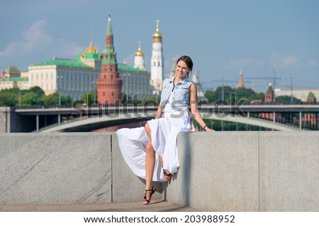 Happy girl in white dress sitting on the parapet of the embankment of the river on the background of the Moscow Kremlin